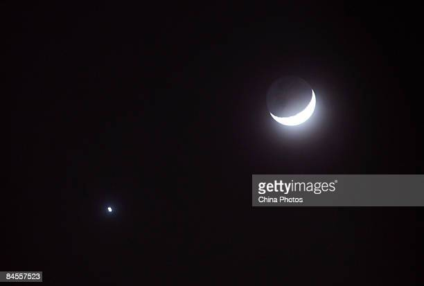 Earth's Moon and the planet Venus are visible in the same part of the sky during Chinese New Year celebrations on January 30 2009 in Beijing China...