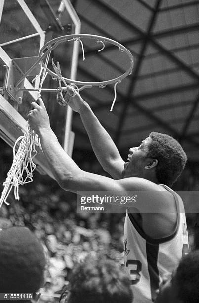 Earvin Johnson Michigan State's most Valuable Player Award winner at the NCAA basketball championship game at Utah University uses a pair of scissors...