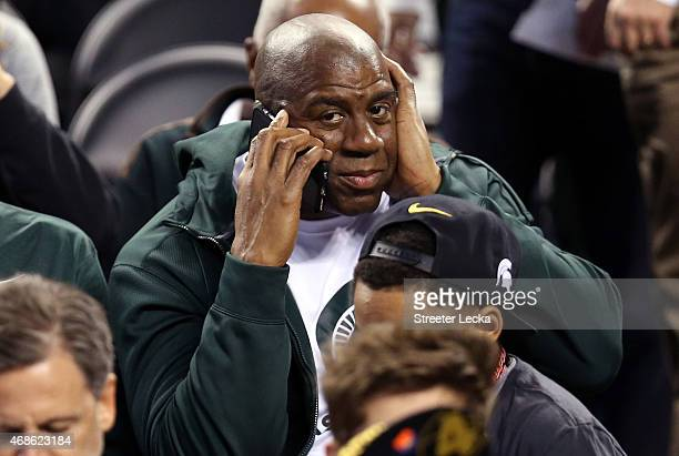 Earvin 'Magic' Johnson is on the phone before the Michigan State Spartans take on the Duke Blue Devils in the NCAA Men's Final Four Semifinal at...