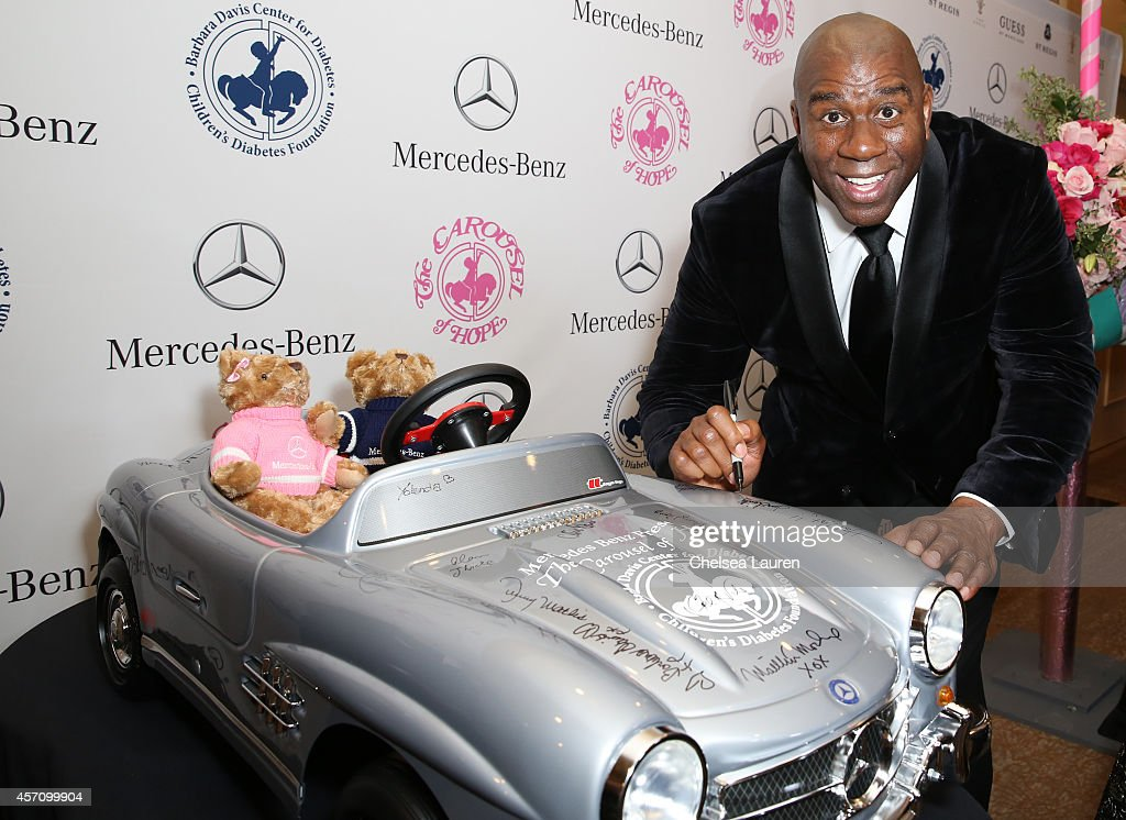 Earvin 'Magic' Johnson Jr autographs a MercedesBenz car for auction at the Carousel of Hope Ball benefitting Barbara Davis Center for Diabetes on...