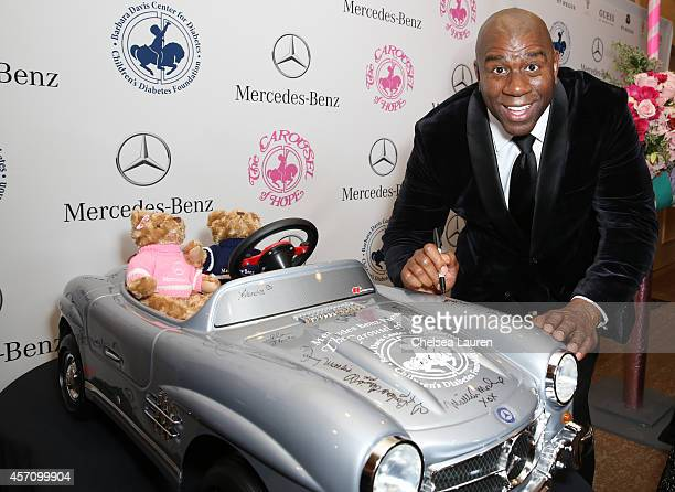 Earvin 'Magic' Johnson Jr autographs a MercedesBenz car for auction at the Carousel of Hope Ball benefitting Barbara Davis Center for Diabetes on...