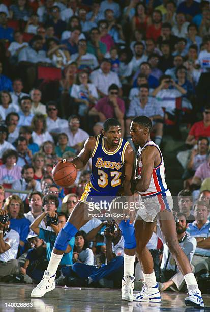 Earvin Magic Johnson of the Los Angeles Lakers backs in on Dennis Rodman of the Detroit Pistons during the 1989 NBA Basketball Finals at The Palace...