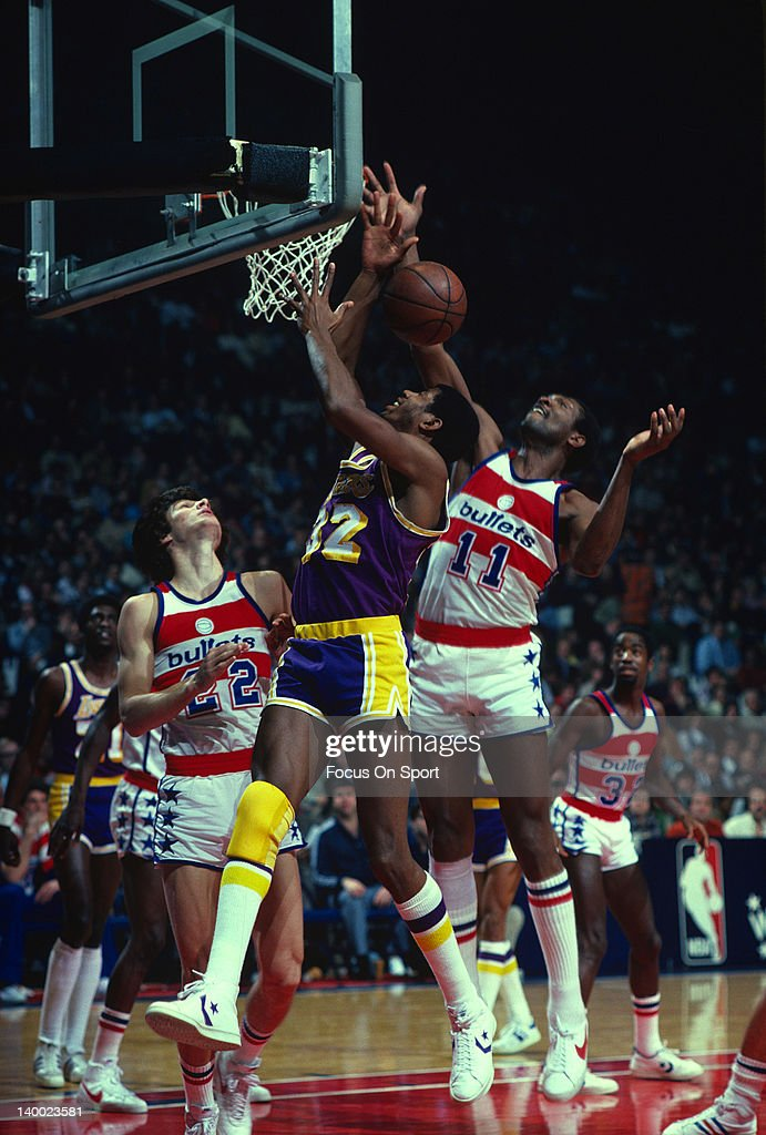 Earvin Magic Johnson of the Los Angeles Lakers battles for a rebound with Elvin Hayes of the Washington Bullets circa 1980 during an NBA basketball...