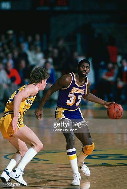 Earvin Magic Johnson of the Los Angeles Lakers dribbles the ball guarded by Pace Mannion of the Golden State Warriors circa 1984 during an NBA...