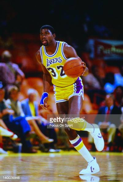 Earvin Magic Johnson of the Los Angeles Lakers dribbles the ball up court during an NBA basketball game circa 1983 at The Forum in Inglewood...