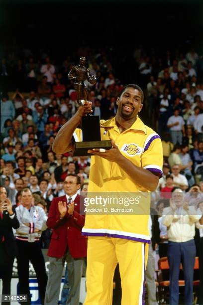 Earvin 'Magic' Johnson of the Los Angeles Lakers holds up the NBA Most Valuable Player Award in 1986 in Inglewood California NOTE TO USER User...