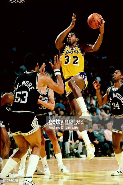 Earvin 'Magic' Johnson of the Los Angeles Lakers takes the ball to the basket against Artis Gilmore of the San Antonio Spurs circa 1985 at The Great...