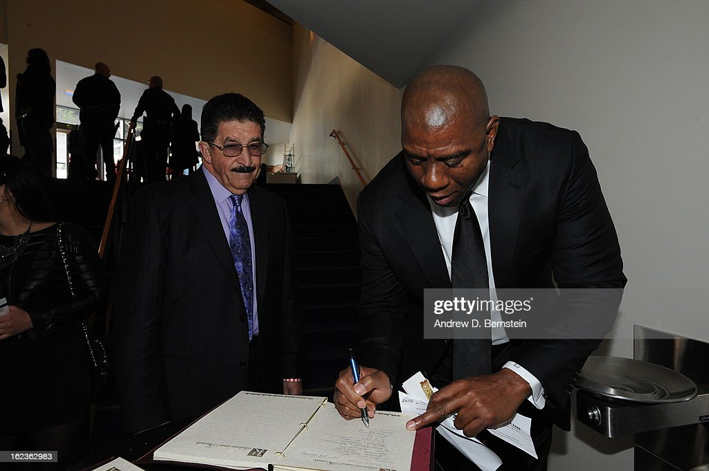 Earvin <a gi-track='captionPersonalityLinkClicked' href=/galleries/search?phrase=Magic+Johnson&family=editorial&specificpeople=157511 ng-click='$event.stopPropagation()'>Magic Johnson</a> signs the guest book before the memorial service for Los Angeles Lakers Owner Dr. Jerry Buss at Nokia Theatre LA LIVE on February 21, 2013 in Los Angeles, California.