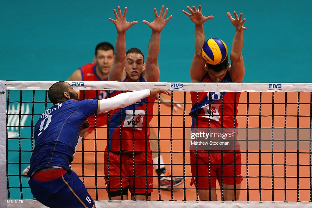 Earvin Ngapeth of France spikes the ball against (R-L) <a gi-track='captionPersonalityLinkClicked' href=/galleries/search?phrase=Marko+Podrascanin&family=editorial&specificpeople=4037691 ng-click='$event.stopPropagation()'>Marko Podrascanin</a> and Marko Ivovic of Serbia during the FIVB World League Group 1 Finals gold medal match between Serbia and France at Maracanazinho on July 19, 2015 in Rio de Janeiro, Brazil.