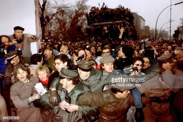 East and West German Police contain the crowd of East Berliners flowing through the recent opening made in the Berlin wall at Potsdamer Square on...