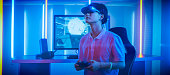 East Asian Pro Gamer Wearing Virtual Reality Headset Plays Online Video Game Shooter using Joysticks / Controllers as Swords. Cool Retro Neon Colors in the Room.