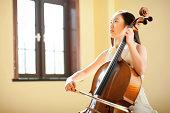 East asian teenage girl playing cello