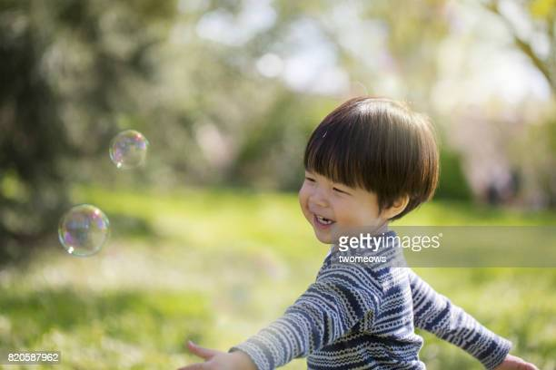 East asian young boy running chasing soap bubble.
