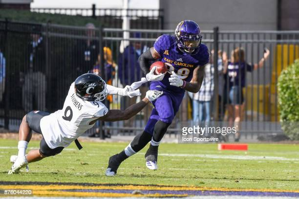 East Carolina Pirates running back Hussein Howe gets past Cincinnati Bearcats cornerback Linden Stephens during a college football game between the...