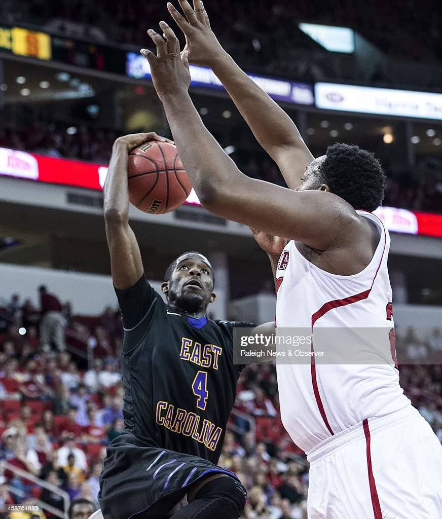 East Carolina's Prince Williams (4) looks to get off a shot against North Carolina State defender Beejay Anya (21) during game action at PNC Arena in Raleigh, N.C., Saturday, Dec. 21, 2013. N.C. State defeated ECU, 90-79.