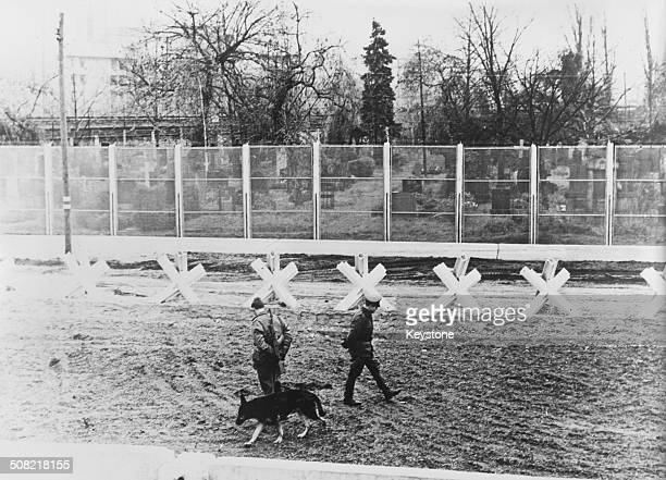 East German border guards seen from Wedding in West Berlin on patrol with a guard dog in the 'death strip' between the fences of the Berlin Wall...