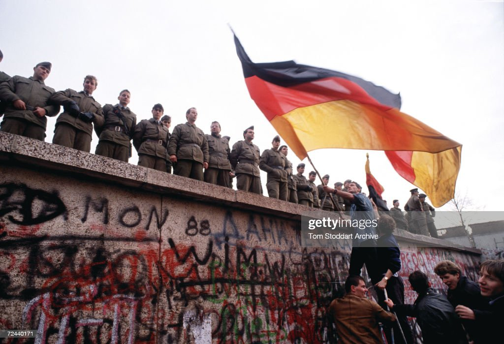East German border guards try to prevent a crowd climbing onto the Berlin Wall on the morning that the first section was pulled down.
