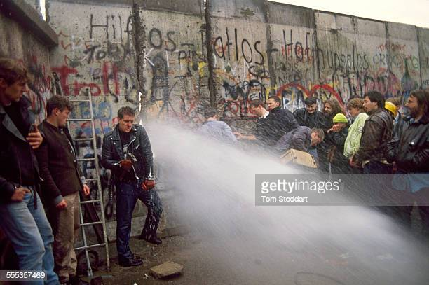 East German border guards with water cannon attempt to stop the first section of the Berlin Wall being torn down by jubilant crowds on the morning of...