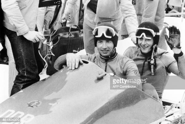 East Germans Meinhard Nehmer and Bernhard Germeshausen are all smiles 06 February 1976 in Innsbruck after winning the gold medal in the twoman...