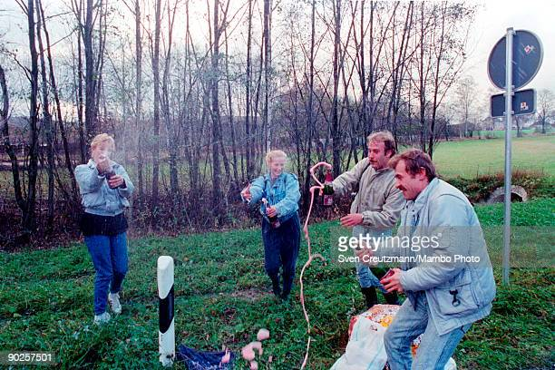 East Germans open sparkling wine bottles to celebrate their arrival in West Germany after crossing the border between Czechoslovakia and West Germany...