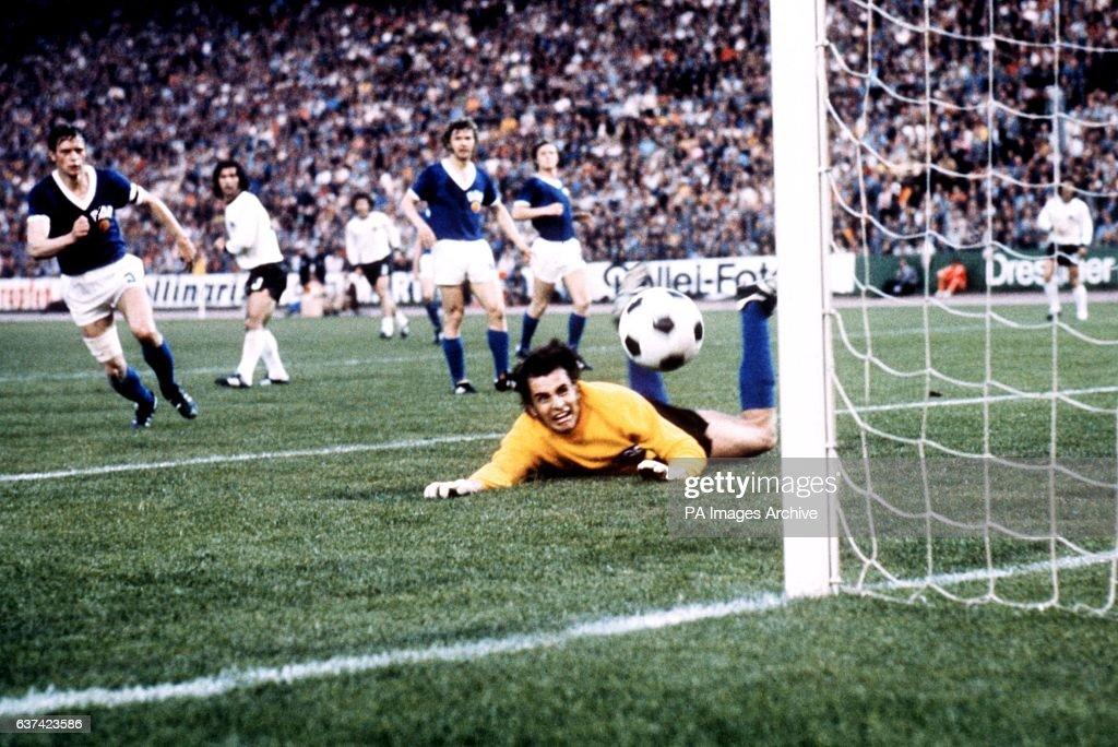 East Germany goalkeeper Jurgen Croy (r) watches in anguish as the ball evades his dive and hits the post before rebounding to safety. East Germany captain Bernd Bransch (l) and West Germany's Gerd Muller (second l) look on