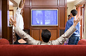 East Indian family celebrating around television