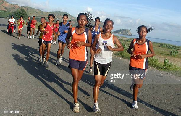 East Timor national sports heroine Aguida Amaral runs with a group of Timorese youths in Dili on June 17 2010 Amaral 36yearold former refugee is one...