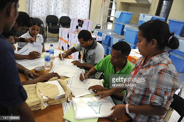 East Timorese election workers prepare polling materials and ballot boxes at the government district office in the capital city of Dili on March 12...