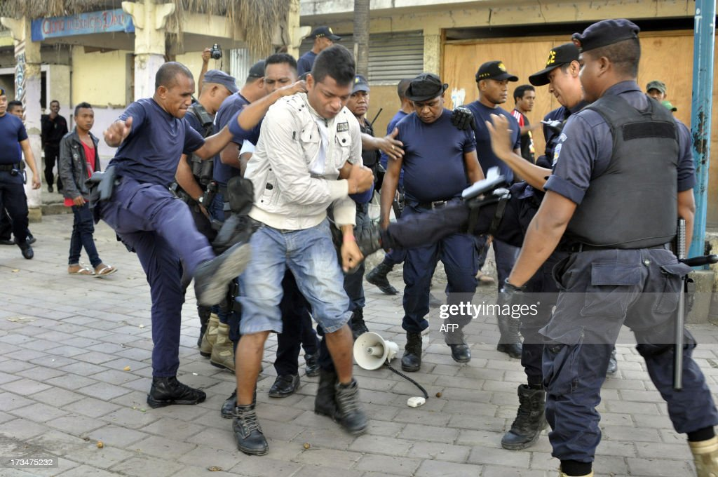 East Timorese police kick an illegal settler during an eviction at the compound of abandoned Hotel Regende in Dili on July 15 2013 About 200 people...