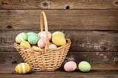 Easter basket filled with hand painted eggs over a rustic wooden background