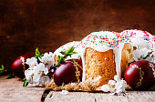 Traditional Russian Easter cakes kulich, with colored red eggs, vintage wooden background, selective focus