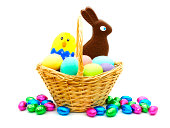 Easter basket filled with colorful eggs and candy over white