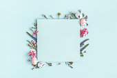 Easter composition. Easter eggs, flowers, paper blank on pastel blue background. Flat lay, top view, copy space