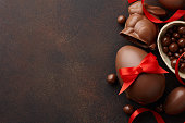 Easter composition with chocolate eggs and bunny decorated with red ribbon on dark brown background, holiday concept