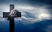 Easter cross with crown of thorns against blue sky abstract background with empty space closeup