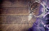 Easter Crown of Thorns with Nails and Royal Purple Robe on Old Wood Background with Copy Space