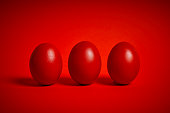 Easter decoration with three colorful eggs on a red background