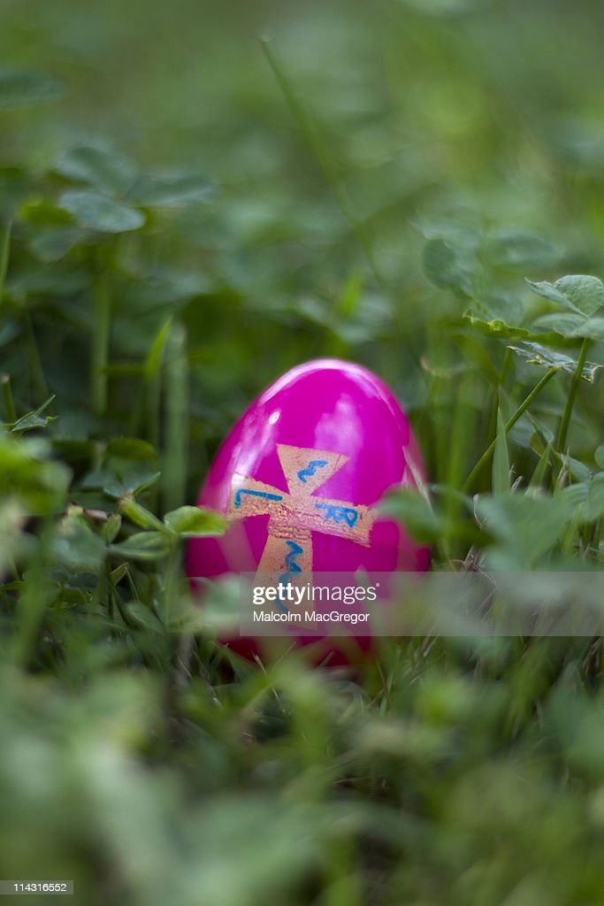 Easter Egg With Cross Design In Tall Grass Stock Photo