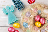 Easter eggs and angel candle on light rustic wooden table. Holiday background.