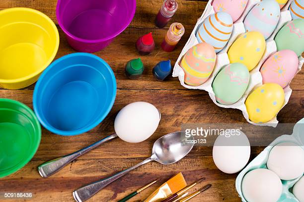 Easter eggs being decorated on wooden table. Decorating supplies.