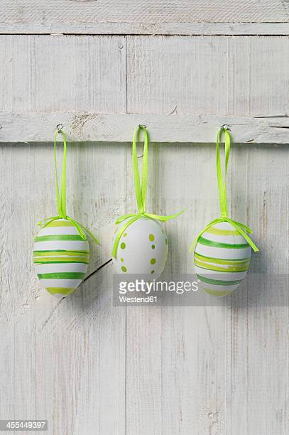 Easter eggs hanging on wooden door, close up