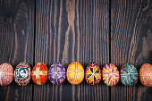 Easter eggs in a row on a dark wooden background.