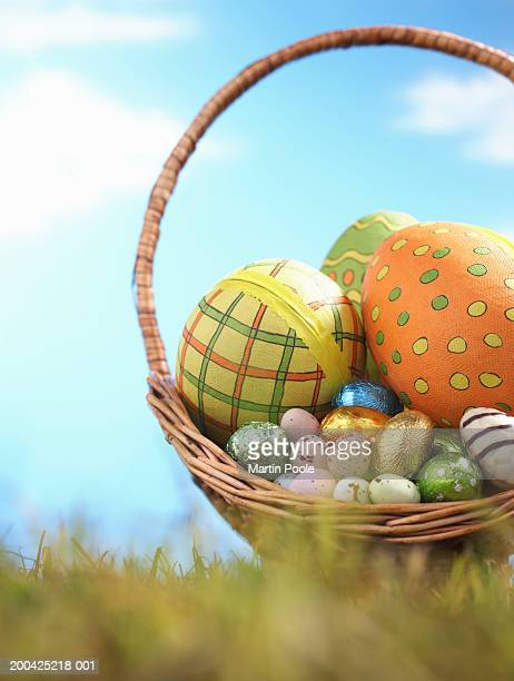 Easter eggs in basket on grass, ground view (focus on basket)