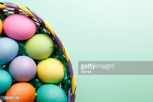 Easter eggs in Easter basket on green background