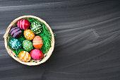 Easter eggs on blackboard in basket