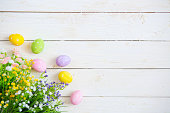 Easter eggs with flowers on white old wooden background.