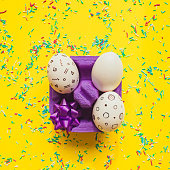 Easter eggs with memphis style print  with bow in box on yellow bright background with confetti.  Happy spring holidays concept.