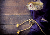 Easter - Jesus jeweled gold kings crown, royal purple robe against a wooden background with textured effect. Selective focus