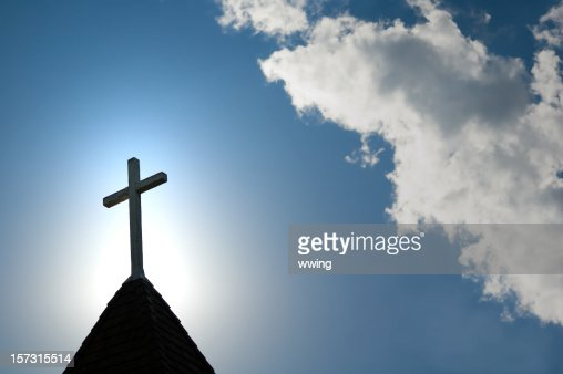 Easter morning with the sun behind a church steepl cross.