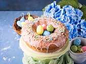 Easter bundt ring cake with sugar frosting sprinkles decorations eggs and hydrangea flowers on blue background. Festive holiday home made sweet food treat